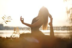 Young woman practicing yoga exercise at river beach and city background stock photography