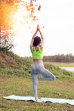 Young woman practicing yoga exercises outdoor in park,  relax in Royalty Free Stock Images