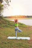 Young woman practicing yoga exercises outdoor in park,  relax in Stock Images