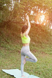 Young woman practicing yoga exercises outdoor in park,  relax in Stock Photo