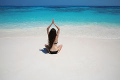 Young woman practicing yoga on the exotic beach with blue water Royalty Free Stock Photo