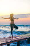 Young woman is practicing yoga with first ray of sunshine on ocean background. Healthy, sport concept lifestyle Royalty Free Stock Images