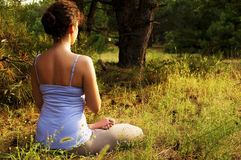 Young woman practicing yoga in the forest. Girl sitting in the lotus position on the grass in the forest Stock Images