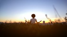 Young woman practicing yoga on hill at sunset, sitting in lotus pose, meditating stock image