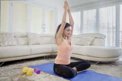 Young woman practicing yoga at home stock image