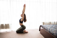 Young woman practicing yoga at home on floor in the morning. Young woman practicing yoga at home in morning Royalty Free Stock Image