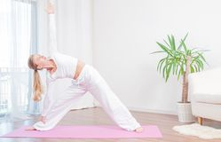 Young woman is practicing yoga at home on mat, girl doing Utthita Trikonasana exercise, extended triangle pose stock photos