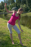 The young woman practicing yoga by the lake Stock Photos