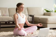 Young woman practicing yoga with laptop, meditating alone at hom Stock Photos