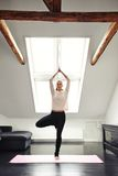 Young woman practicing yoga in living room Royalty Free Stock Photos