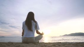 Young woman practicing yoga on the beach at sunrise. Young woman practicing yoga in lotus pose on the beach at sunrise stock video footage