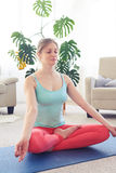 Young woman practicing yoga in lotus pose indoor Stock Photo