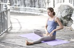 Young woman practicing yoga during yoga retreat in Asia, Bali, meditation, relaxation in abandoned temple royalty free stock images