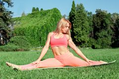 Healthy Lifestyle. Woman practicing yoga on mat outdoors doing split stretching concentrated royalty free stock photos