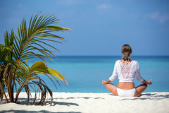 Young woman practicing yoga meditation on the beach facing the ocean near a palm tree on Maldives.  Royalty Free Stock Photo