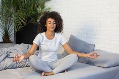 Young woman practicing yoga meditation on her bed royalty free stock images