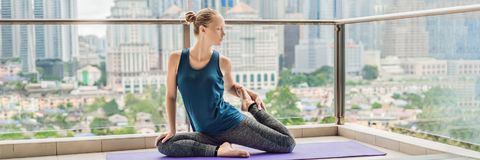 Young woman is practicing yoga in the morning on her balcony with a panoramic view of the city and skyscrapers BANNER, long format stock image