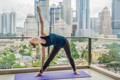 Young woman is practicing yoga in the morning on her balcony wit. H a panoramic view of the city and skyscrapers Stock Images
