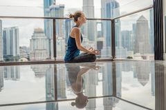Young woman is practicing yoga in the morning on her balcony wit. H a panoramic view of the city and skyscrapers Stock Photography