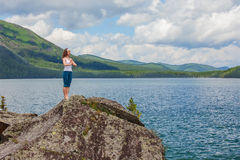 Young woman is practicing yoga at mountain lake Stock Photos