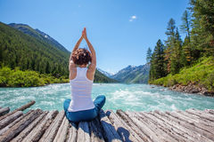 Young woman is practicing yoga at mountain river Stock Photo