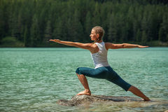 Young woman is practicing yoga at mountain river Royalty Free Stock Photography