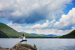 Young woman is practicing yoga at mountain river Stock Photos