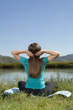 Young woman is practicing yoga at mountain river Royalty Free Stock Photo