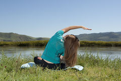 Young woman is practicing yoga at mountain river Stock Image