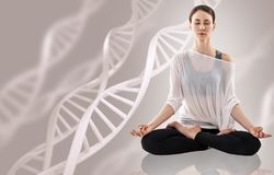 Young woman practicing yoga near big molecule chain. Young woman practicing yoga, sitting in a lotus position near big molecule chain. Over beige background Stock Photo