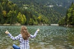 Young woman practicing  yoga near a mountain lake Stock Photography