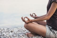 Young woman practicing yoga near the sea. Harmony and meditation concept. stock images