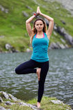 Young woman practicing yoga outdoor. Young woman practicing yoga by a lake in the mountains Stock Images