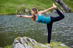Young woman practicing yoga outdoor. Young woman practicing yoga by a lake in the mountains Royalty Free Stock Image