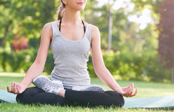 Young woman practicing yoga outdoors at the park. Cropped shot of a young woman smiling while meditating outdoors at the park sitting in lotus position yoga Royalty Free Stock Image