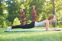 Young woman practicing yoga outdoors at the park royalty free stock photo