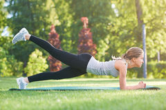 Young woman practicing yoga outdoors at the park. Shot of a young fitness woman working out outdoors at the park doing plank exercise lifting her leg in the air Royalty Free Stock Images