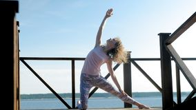 Young woman practicing yoga outdoors in summer. Healthy lifestyle stock video footage