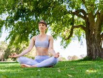 Young woman practicing yoga in the park Royalty Free Stock Images