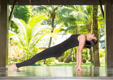 Young woman is practicing yoga and pilates on nature. Stock Photos
