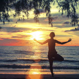 Young woman practicing yoga in the rays of the surrealist sunset at seaside. Stock Images
