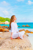 Young woman practicing yoga on the rock Royalty Free Stock Photos