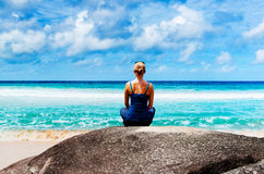 Young woman practicing yoga on the rock Stock Photos
