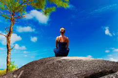 Young woman practicing yoga on the rock Royalty Free Stock Image