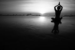 Young woman practicing yoga on the sea beach. Black and white high contrast photography. Silhouette of young woman practicing yoga on the sea beach. Black and Royalty Free Stock Photography