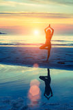 Young woman practicing yoga on sea beach at surrealistic sunset. Stock Photos