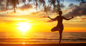 Young woman practicing yoga by the sea at sunset. Nature. Stock Images