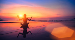 Young woman practicing yoga by the sea at sunset. Travel. Stock Image