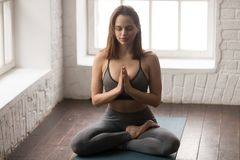 Young woman practicing yoga, sitting in Lotus pose, Padmasana exercise royalty free stock photos