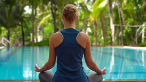 Young woman practicing yoga sitting in a lotus posture on a yoga mat near the pool in the tropics.  stock footage
